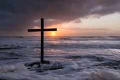 storm-sunset-cross-black-waters-as-sun-sets-over-sea-45353570